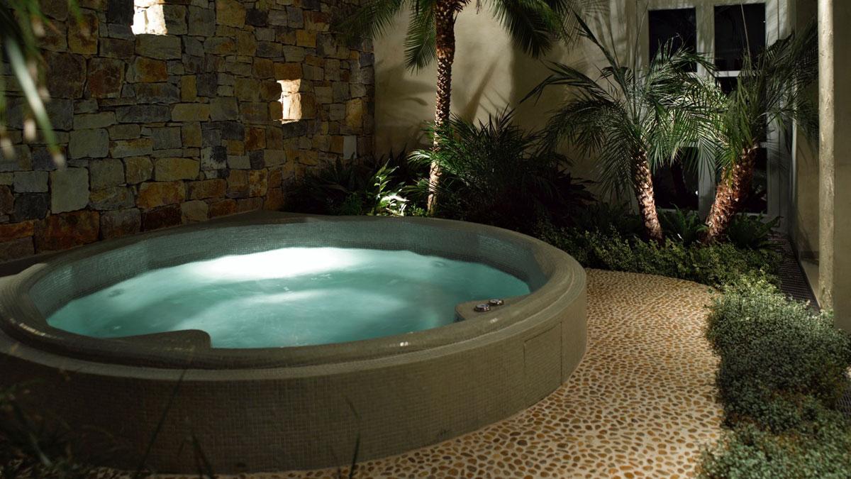 Whirlpool außen und innen mit Glasmosaik überzogen, am Boden Naturstein aus Flachkieselsteinen, Bruchsteinmauer